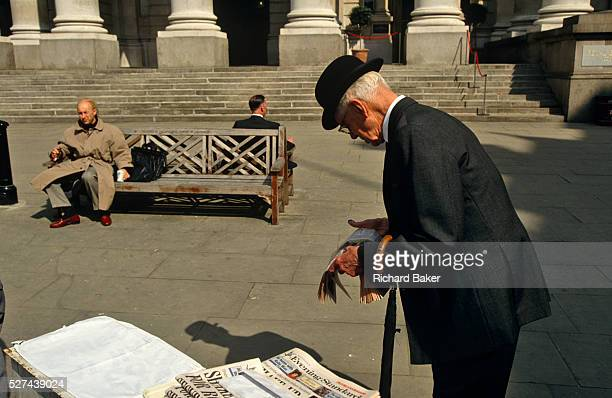 An elderly gentleman wearing a traditional bowler hat and carrying an umbrella, pauses to read the headlines in the London Evening Standard...