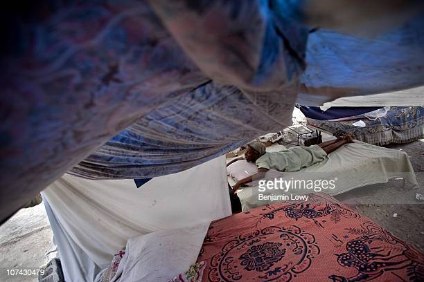 An elderly Haitian woman sleeps outdoors in a tent made of scavenged bed sheets in the Dante's Viullage neighborhood in Port au Prince on February 6...