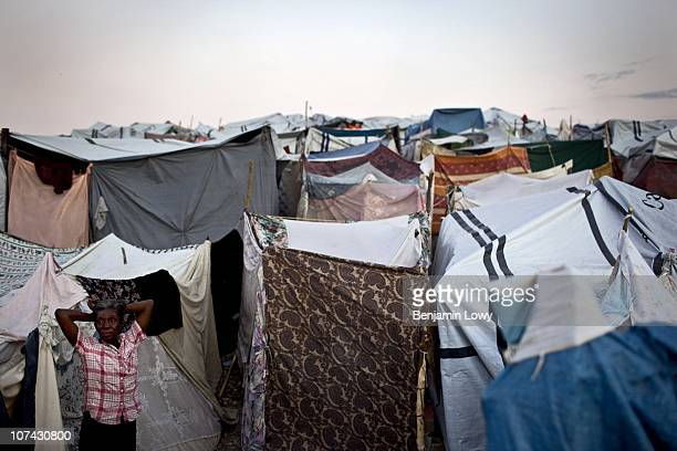 An elderly Haitian woman stretches outside her tent in the sprawling Delmas Airport Road IDP camp on February 10 2010.Haiti was struck by a magnitude...