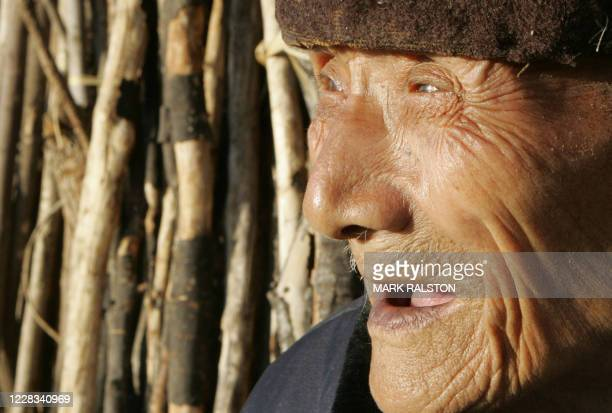 An elderly Hakka man outside his old circular Tulou earth house, which are the traditional homes of China's minority Hakka people, in Shuyang...
