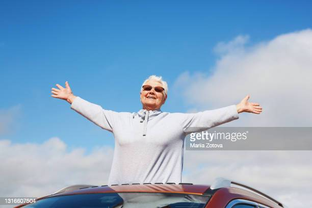 an elderly happy healthy woman on the background of a blue sky smiles, has fun and looks out of the car hatch - lifestyle stock pictures, royalty-free photos & images