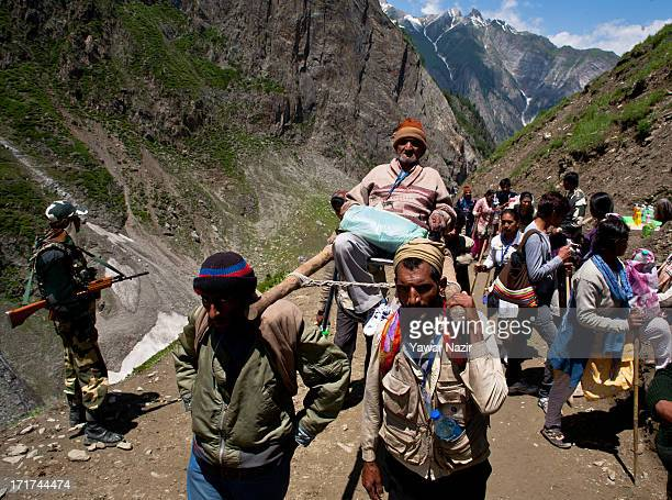 An elderly Hindu pilgrim is carried by palanquin bearers as she makes her pilgrimage to the sacred Amarnath Caves one of the most revered of Hindu...
