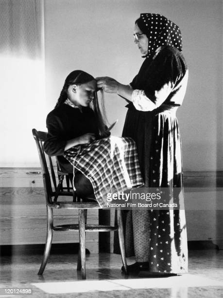 An elderly Hutterite woman is braiding the hair of a young Hutterite girl Northeast Alberta Canada 1963 Photo taken during the National Film Board of...