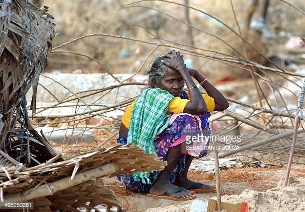 An elderly Indian Dalit woman sits in front of her home in the village of Keshvanpalayam some 30 kms from Nagapattinam07 January 2005 India's...