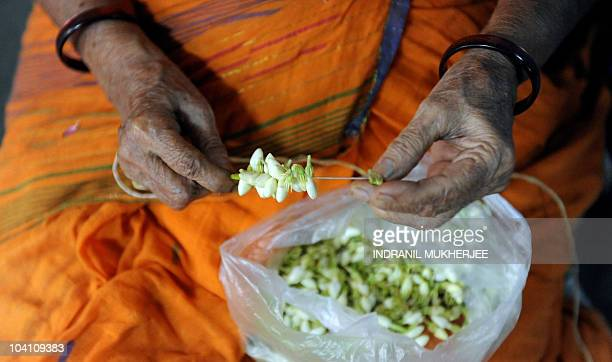 An elderly Indian Hindu woman strings together a jasmine garland to offer to an idol of the elephantheaded god Lord Ganesha at a temple in Mumbai on...