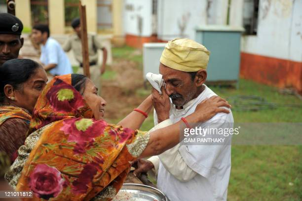 An elderly Indian inmate at Sabarmati Central Jail mourning the recent death of his wife is comforted by his siters during 'Raksha Bandhan' in...