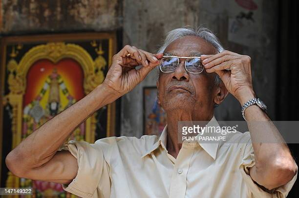 An elderly Indian man adjusts his spectacles as he watches share prices on the digital brodcast outside the Bombay Stock Exchange in Mumbai on April...