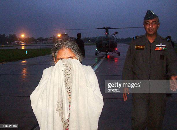 An elderly Indian woman cries while being escorted by an Indian Air Force officer as they walk across the tarmac at Vadodara Air Force Station 12...