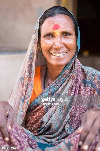 An elderly Indian woman squats in front of a house She is smilling and looks into the camera She wears a traditional colorful hairscarf As Hindu...