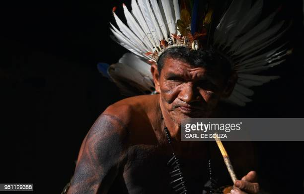 An elderly indigenous man from the Potiguara tribe smokes during a ceremony at the Acampamento Terra Livre in Brasilia on April 25 2018 Approximately...
