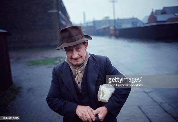 An elderly inhabitant of Oldham Greater Manchester carries a loaf of bread under his arm in 1965