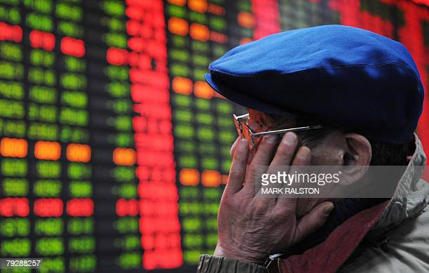 An elderly investor watches a stock price board showing the green colouring which indicates falling prices at a private securities firm in Shanghai...