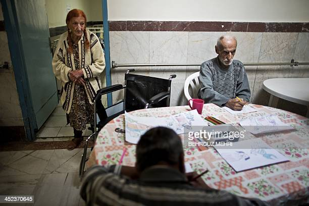 An elderly Iranian Jewish woman watches men colouring at the Iranian Jewish care home for the elderly in Tehran on November 27 2013 The Jewish care...