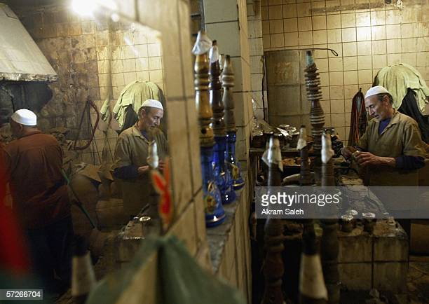 An elderly Iraqi man is reflected in a mirror as he prepares shisha or hubblybubbly at a tea shop April 6 2006 in Baghdad Iraq According to the US...