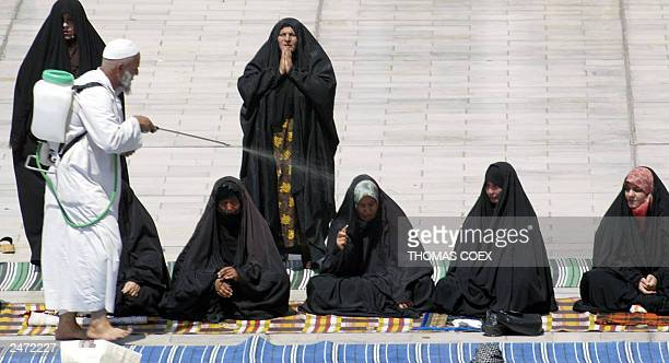 An elderly Iraqi sprays water to cool chadoreclad Shiite Muslim women in the hot midday sun during Friday prayers at the the Shiite Kadhimiya mosque...