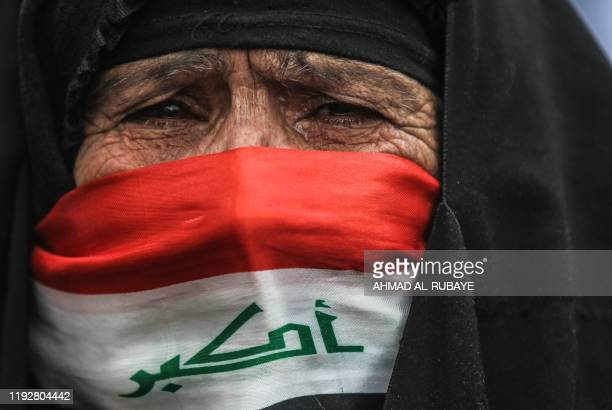 TOPSHOT An elderly Iraqi woman her face covered with a national flag cries as she watches antigovernment demonstrators protesting in the capital...