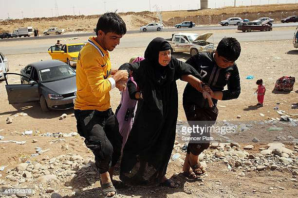 An elderly Iraqi woman is helped into a temporary displacement camp for Iraqis caughtup in the fighting in and around the city of Mosul on June 26...