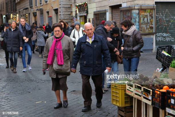 An elderly Italian couple walk holding hands to the iconic Campo di Fiori market where in recent years Bangladeshi migrants have taken over most of...