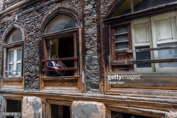 An elderly Kashmir Muslim woman sits on the window of her house in the old city on March 13 2019 in Srinagar the summer capital of Indian...