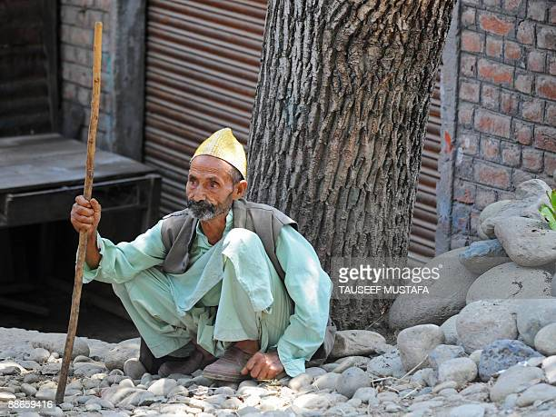 An elderly Kashmiri man listens to unseen chief cleric and All Parties Hurriyat Confrence chairman Mirwaiz Umar Farooq addresses a protest rally in...