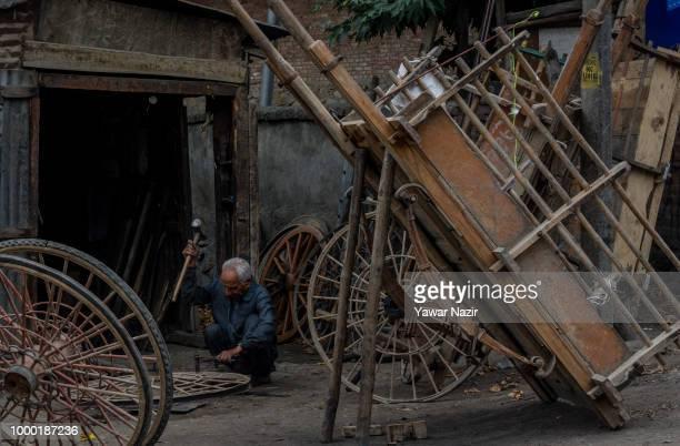 An elderly Kashmiri Muslim blacksmith makes wagon wheels in a market on July 16 2018 in Budgam west of Srinagar the summer capital of Indian...