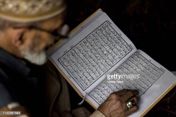 An elderly Kashmiri Muslim cleric recites Holy Quran at the Dastgeer Sahib shrine of 11th century Sufi preacher Sheikh Abdul Qadir Jeelani during...