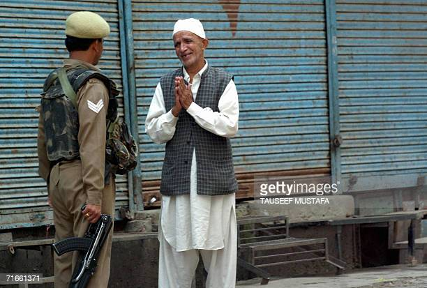 An elderly Kashmiri Muslim gestures as he speaks with an Indian Central Reserve Police Force soldier during a cordon and search operation at Kukar...