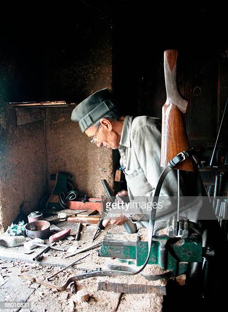An elderly Kashmiri Muslim gunsmith works on a 12 gauge