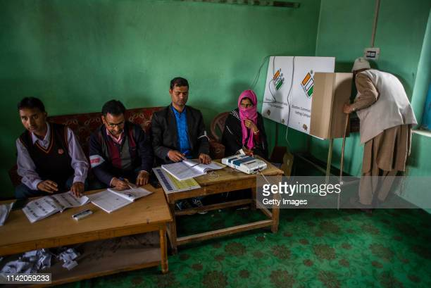 An elderly Kashmiri Muslim man casts his vote inside a polling station during the first phase of the elections of the lower house of the Indian...