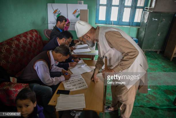 An elderly Kashmiri Muslim man searches his name in the voters list inside a polling station during the first phase of the elections of the lower...