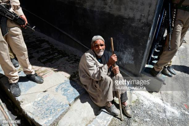 TOPSHOT An elderly Kashmiri muslim sits on a street next to Indian government forces during a antiIndia protest in Srinagar on June 9 2017 Another...