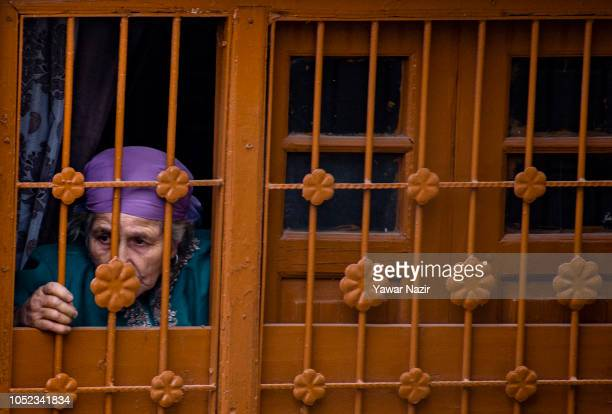 An elderly Kashmiri Muslim woman looks from the window of her house towards the Indian government forces searching the war ravaged residential house...