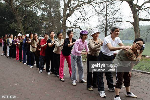 An elderly keep fit class massage each other in a group fitness session besides Hoan Kiem Lake Hanoi Vietnam For a county not know for it's sporting...