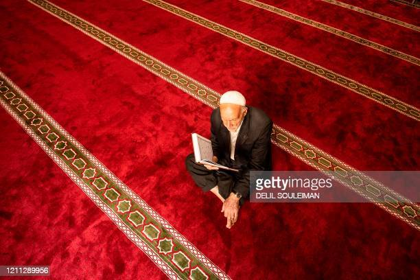An elderly Kurdish man sits reading the holy Koran during the Muslim holy month of Ramadan, at a mosque free of worshippers as authorities close down...