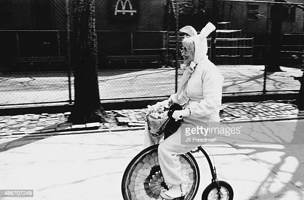 An elderly lady dressed as the Easter Bunny on a small penny farthing in Greenwich Village New York City circa 1980