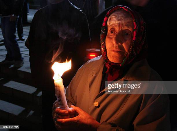 CONTENT] An elderly lady holding a candle in front of the cathedral on Orthodox Easter Chisinau Moldova