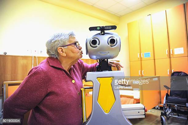 An elderly lady kisses a robot during daily activities of the project RobotEra at nursing residence San Lorenzo on December 19 2015 in Florence Italy...