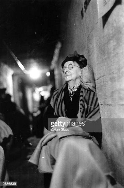 An elderly lady propped up to sleep in an air raid shelter Original Publication Picture Post 308 Scene In An Air Raid Shelter pub 1940