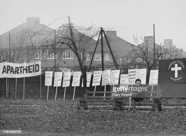 An elderly lady sits on a park bench with placards and a banner beyond following an anti-apartheid march before the rugby international between...