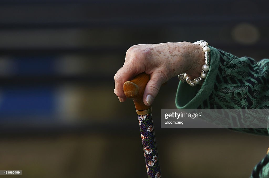 An elderly lady sits with a walking stick in Eastbourne, U.K., on Tuesday, April 1, 2014. Pensioners and savers have seen returns on their money shrink since the financial crisis drove interest rates to a record low. Photographer: Chris Ratcliffe/Bloomberg via Getty Images