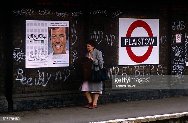 An elderly lady walks past the intimidating backdrop of tagged walls of Plaistow an east London station after the crime of defacement and criminal...