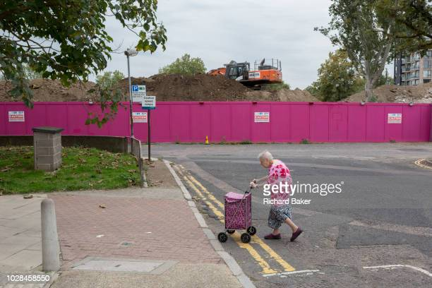 An elderly lady walks slowly with her shopping trolley across a road on the Aylesbury Estate on 4th September 2018 in Southwark London England The...