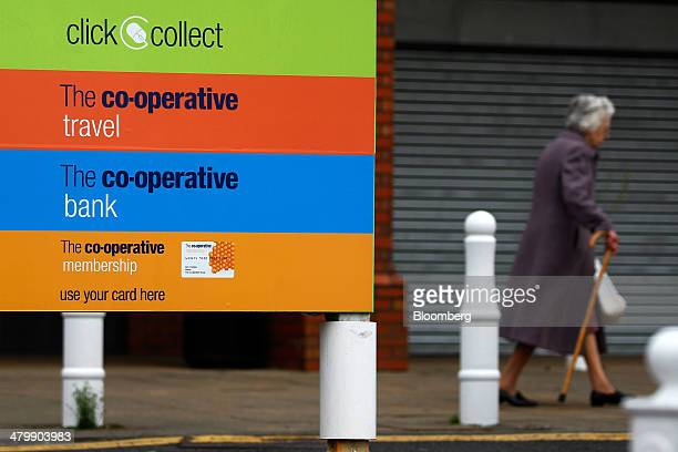 An elderly lady walks with a walking stick as she passes signs for services offered by the CoOperative Group Ltd including 'click and collect' food...