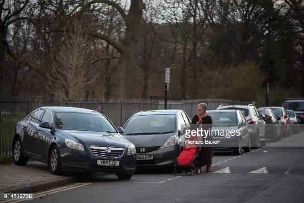 An elderly lady with a child's buggy walks in the road past a mysteriously abandoned Vauxhall car resting at 45 degrees off the road but blocking a...