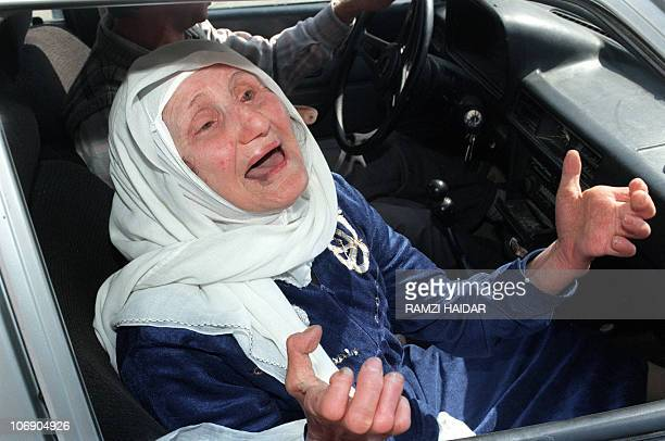 An elderly Lebanese woman cries in pain 19 April 1996 in Qana as she discovers the remains of the Fijian UN compound where her family was killed by...