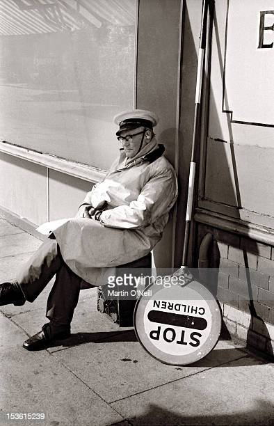 An elderly 'Lollypop' man takes a breather between trips to help youngsters across the road in Eccles Greater Manchester circa 1977