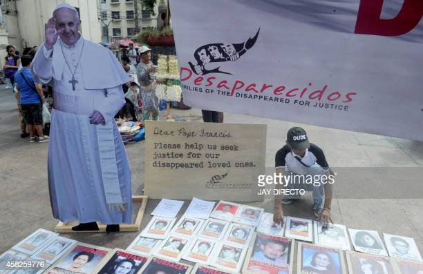 An elderly looks at photos of the disappeared during rally in front of a Roman Catholic Church in Manila on November 2 2014 Members of the...