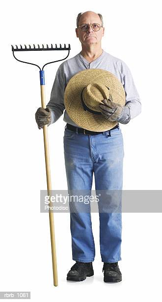 an elderly male farmer with a hat and rake glares sternly into the camera