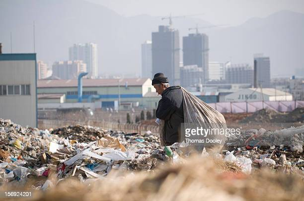 An elderly male migrant worker carries a large bag of plastic bottles he had collected at the Dalian Jinzhou garbage dump China does not have a...