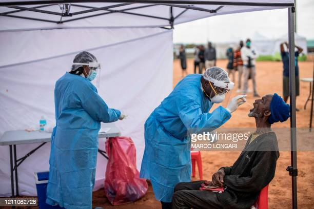 An elderly man, a resident of the sprawling township of Alexandra in Johannesburg, opens his mouth to receive a testing swab for COVID-19 coronavirus...